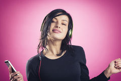 Happy girl listening to music with headphones and dancing. Royalty Free Stock Photos