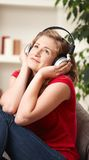 Happy girl listening to music at home Stock Images