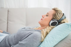 Happy girl listening to music lying on the couch Royalty Free Stock Photo