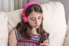 Happy girl listening to music from mobile phone sitting on a cou Stock Photos