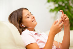 Happy girl listening to music from mobile phone Stock Photography
