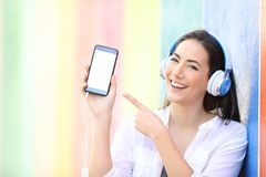 Happy girl listening to music is showing phone screen royalty free stock image
