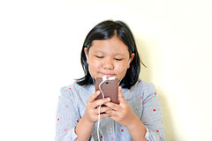 Happy girl listening to the music from a smartphone. Royalty Free Stock Photos