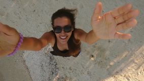 Happy girl with long hair catch quadcopter drone safe by hands on the beach. Safety landing HD aerial above selfie shot. stock video footage