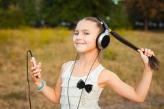 Happy girl with long hair listening song. Happy girl with long hair having nice rest outdoor, pretty girl with black and silver headphone listening song on Royalty Free Stock Image