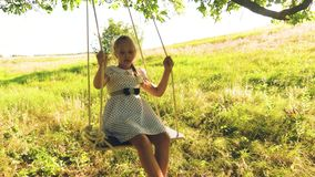 Happy girl with long hair swinging on swing on tree branch. On swing in the park happy girl. Slow motion. girl with long. Hair swings on swing under summer oak stock footage