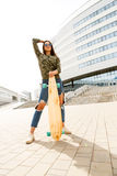 Happy girl with longboard skateboard Royalty Free Stock Image