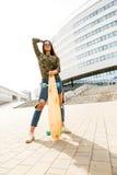 Happy girl with longboard skateboard Royalty Free Stock Image