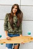 Happy girl with longboard skateboard Stock Image
