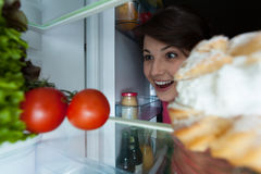Happy girl looking into the fridge Royalty Free Stock Photo