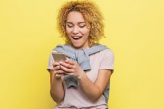 Happy girl is looking at the phone`s screen and smiling. She is excited and happy. Isolated on yellow background. stock photography