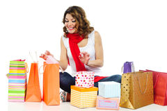 Happy girl looking for present in shopping bags Stock Images