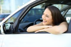 Girl dreaming with a new car. Happy girl looking at side dreaming with a new car Royalty Free Stock Image