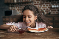 Happy girl looking at sweet jam in bowl for toasts Royalty Free Stock Images