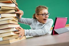 Happy girl looking at the tablet in the same time pushes off the mountain of books. Photo of little girl in classroom. Education concept Stock Images