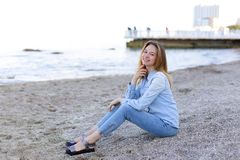 Smiling young woman rests on beach and poses in camera, sitting Royalty Free Stock Photography