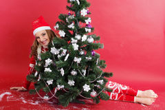 Happy girl looks out from behind christmas tree Stock Photos