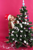 Happy girl looks out from behind christmas tree Stock Images