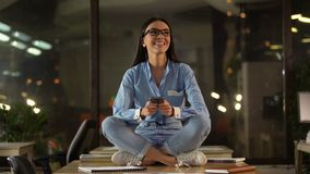 Happy girl in lotus position using cell phone in office, break time at work stock video