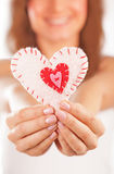 Happy girl in love. Picture of a small white heart in hands, female holds handmade sewn soft toy, macro, shallow dof, woman with Valentine gift, happy girl stock photography