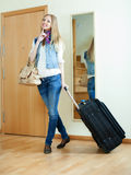 Happy girl with luggage near door Stock Photo