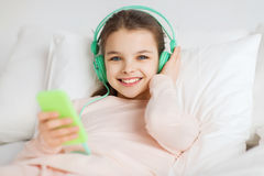 Happy girl lying in bed with smartphone at home Royalty Free Stock Image