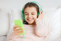 Happy girl lying in bed with smartphone at home Royalty Free Stock Photos