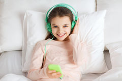 Happy girl lying in bed with smartphone at home Royalty Free Stock Photo