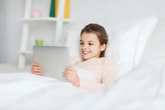 Happy girl lying in bed with tablet pc at home Stock Image