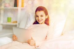 Happy girl lying in bed with tablet pc at home. People, children and technology concept - happy smiling girl lying awake with tablet pc computer in bed at home Stock Images