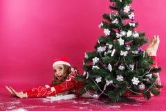 Happy girl is lying behind christmas tree Stock Image