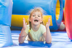 Happy girl lying on big inflatable trampoline game Royalty Free Stock Photo