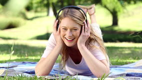 Happy girl lying on blanket listening to music in the park Royalty Free Stock Photos