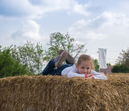 Happy girl lying down on hay. Blonde girl lying down on brown hay at the vacation Royalty Free Stock Photos