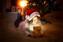 Happy girl lying on floor and looking inside of magic gist box Royalty Free Stock Images