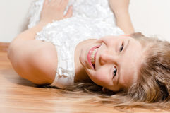 Happy girl lying on floor smiling and looking into camera Stock Image