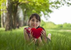 Happy girl. Lying on the grass with fluffy heart in her hands Royalty Free Stock Photos