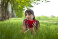 Happy girl lying on the grass. With a red heart in her hands Royalty Free Stock Photos