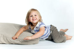 Happy girl lying on the grey pillow Royalty Free Stock Image
