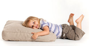 Happy girl lying on the grey pillow Royalty Free Stock Photos