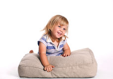 Happy girl lying on the grey pillow Royalty Free Stock Photo