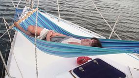 Happy girl lying in hammock on sailing yacht, perfect vacation. Stock footage stock video footage