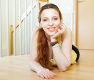 Happy girl lying on hardwood floor Stock Image