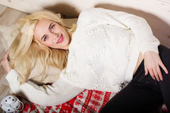 Happy girl is lying at home on pillows and blanket. Happy pretty smiling blonde girl is wearing warm sweater lying on pillow and blanket, winter concept Royalty Free Stock Photos