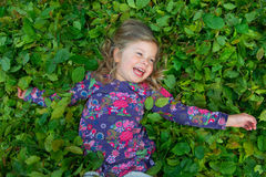 Happy girl is lying in leaves Stock Photos