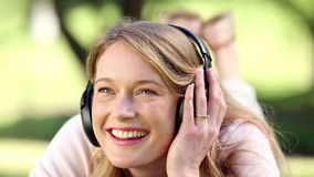 Happy girl lying and listening to music in the park Stock Photo