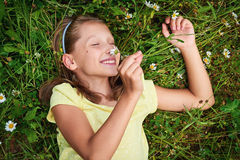 Happy girl lying in meadow between camomiles smelling the flower Stock Images