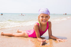 Happy girl lying on the sand near the water on the beach and smiling happily looks into the frame. Happy girl lying on the sand near the water on beach and Royalty Free Stock Image