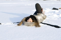 Happy girl lying in snow Royalty Free Stock Image