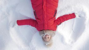 Happy girl lying on a snow and shows angel. A pretty girl in a coat lies on the snow, spreading her arms. Happy girl lying on a snow and shows angel. A pretty stock video